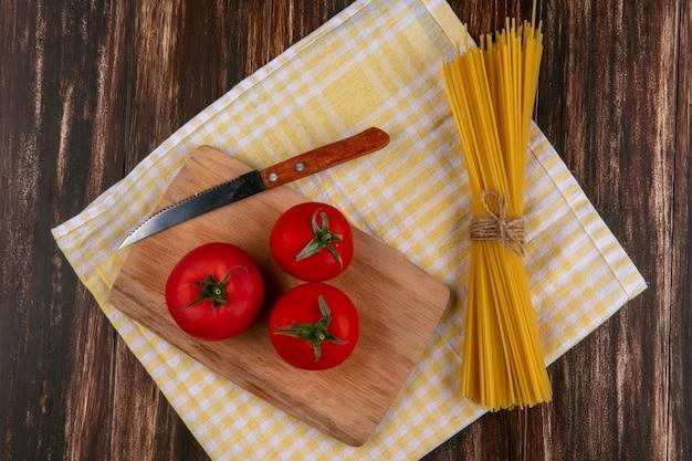 Vista dall'alto di spaghetti crudi con pomodori su un tagliere con un coltello su un asciugamano a scacchi giallo su una superficie di legno