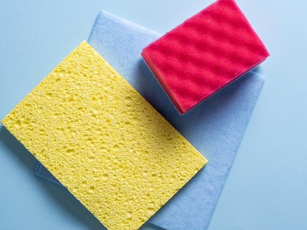 Vista dall'alto di spugne per la pulizia di diversi colori e dimensioni disposte su blu