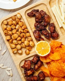 Vista dall'alto di spuntini di birra assortiti come dushbara fritto alla griglia pollo e patatine fritte su una tavola di legno