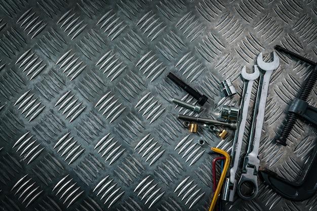 Vista dall'alto di strumenti sulla piastra di controllo industriale in metallo. checkerplate in metallo per antiscivolo. dado, bulloni e chiave esagonale sul pavimento in lamiera. terra argentata.