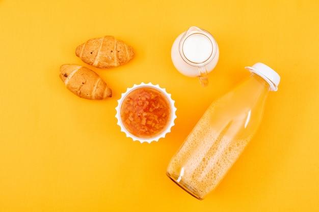 Vista dall'alto di succo con cornetti e marmellata, latte su superficie gialla orizzontale