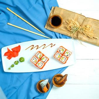 Vista dall'alto di sushi set rotoli con crema di granchio con crema di formaggio e avocado nel caviale di pesce volante con salsa di soia su blu e bianco