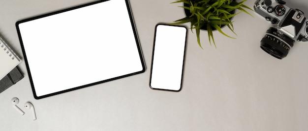 Vista dall'alto di tablet e smartphone con schermo vuoto sul tavolo bianco con fotocamera, cancelleria e accessori, tracciato di ritaglio.