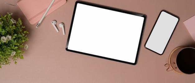 Vista dall'alto di tablet e smartphone con schermo vuoto sul tavolo rosa con cancelleria e accessori, tracciato di ritaglio.