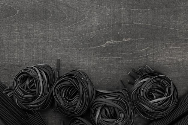 Vista dall'alto di tagliatelle nere con spazio di copia