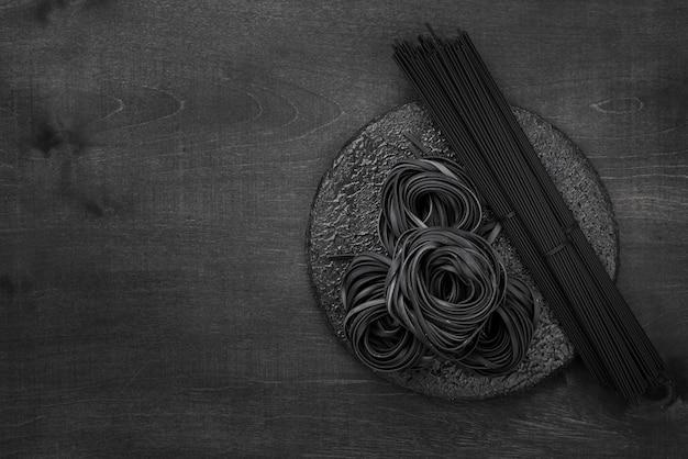 Vista dall'alto di tagliatelle nere e spaghetti con copia spazio