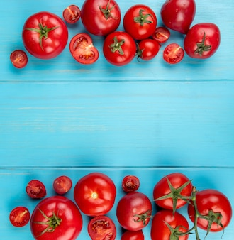 Vista dall'alto di taglio e interi pomodori sulla superficie blu con spazio di copia