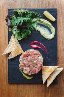 Vista dall'alto di tartare di tonno rosso piccante con salsa agrodolce e piccante.
