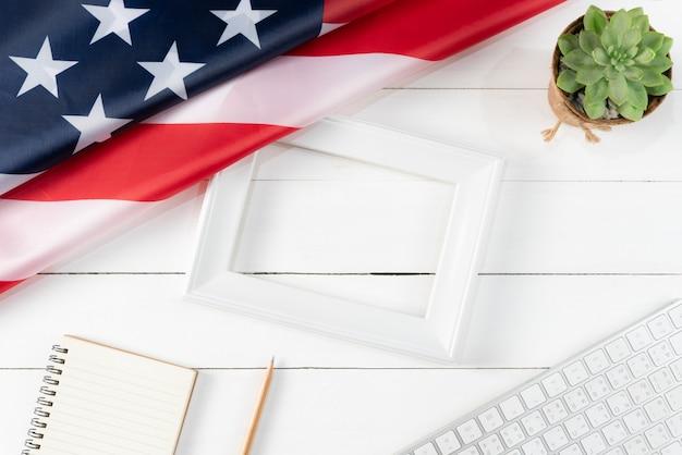 Vista dall'alto di tastiera, libro, matita, cornice bianca e bandiera americana su fondo di legno bianco