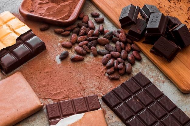 Vista dall'alto di tavolette di cioccolato con polvere di cacao e fagioli crudi