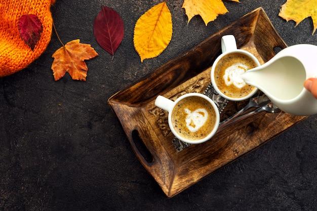 Vista dall'alto di tazze di caffè intorno a foglie gialle