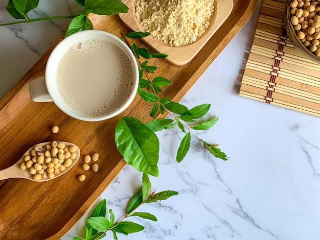 Vista dall'alto di tazze di latte di soia, semi di soia sul cucchiaio di legno e latte di soia in polvere in un piatto di legno