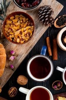 Vista dall'alto di tazze di tè con uvetta secca in una ciotola su rustico