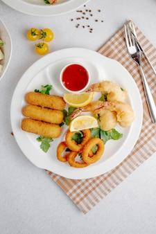 Vista dall'alto di tempura di calamari e gamberi e bastone di formaggio fritto su un piatto bianco
