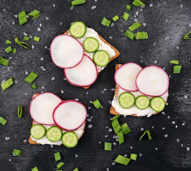 Vista dall'alto di toast con ravanello e cetriolo su superficie nera orizzontale