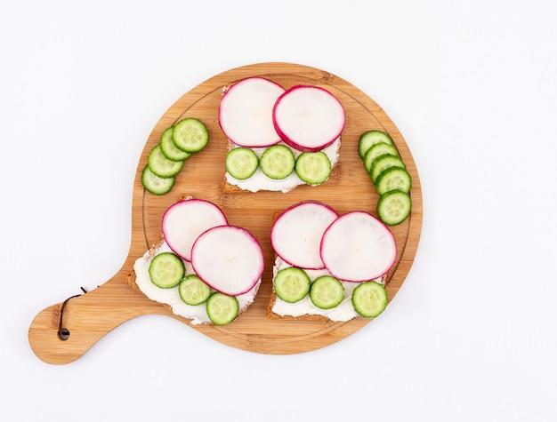 Vista dall'alto di toast con ravanello e cetriolo sul tagliere e su superficie bianca orizzontale