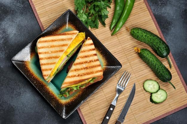 Vista dall'alto di toast sandwich con lattuga, prosciutto, uova