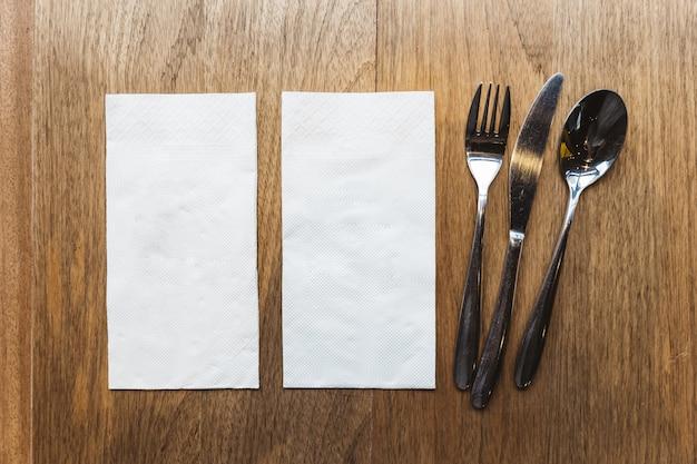 Vista dall'alto di tovaglioli di tessuto e posate sul tavolo di legno. per banner di cibo.