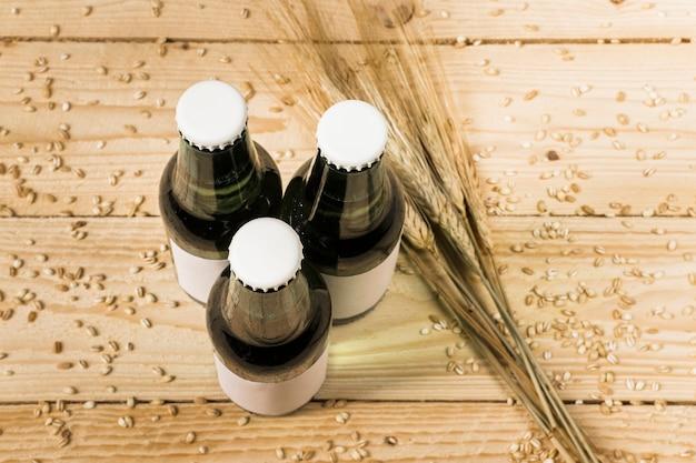Vista dall'alto di tre bottiglie di birra chiuse e spighe di grano su fondo in legno
