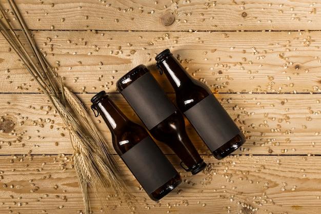 Vista dall'alto di tre bottiglie di birra e spighe di grano sulla tavola di legno