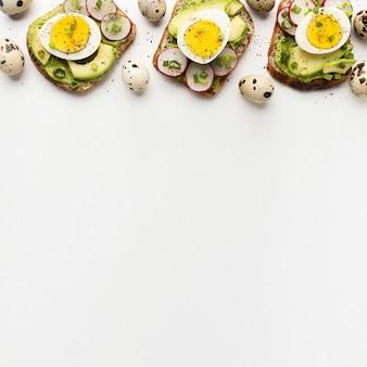 Vista dall'alto di tre panini con uova e avocado con spazio di copia