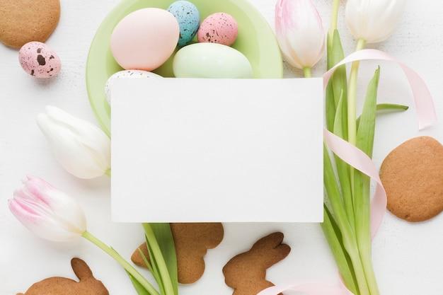 Vista dall'alto di tulipani e uova di pasqua colorate con pezzo di carta in cima
