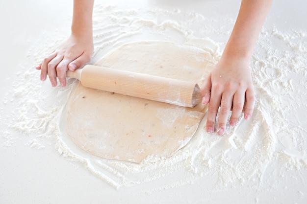 Vista dall'alto di un bambino che produce pasta per pizza su un tavolo leggero