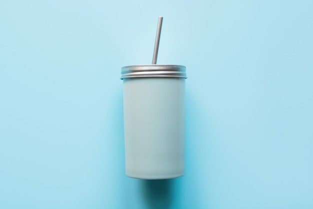 Vista dall'alto di un barattolo riutilizzabile con un coperchio di metallo e una cannuccia per le bevande estive.