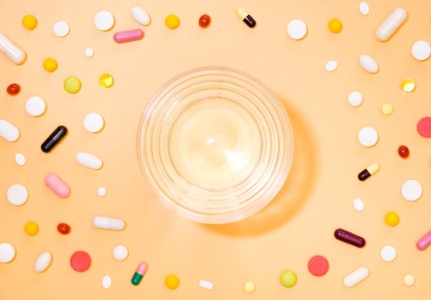 Vista dall'alto di un bicchiere d'acqua con le pillole