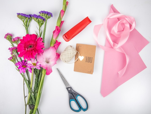 Vista dall'alto di un bouquet di fiori rosa gerbera e gladiolo con statice e una cucitrice rossa con forbici nastro rosa e piccola cartolina su sfondo bianco