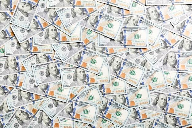 Vista dall'alto di un centinaio di banconote in dollari fatte come sfondo. valuta usd. trama di dollari americani