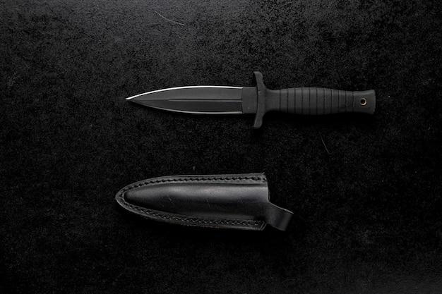 Vista dall'alto di un coltello da combattimento con custodia nera su un tavolo