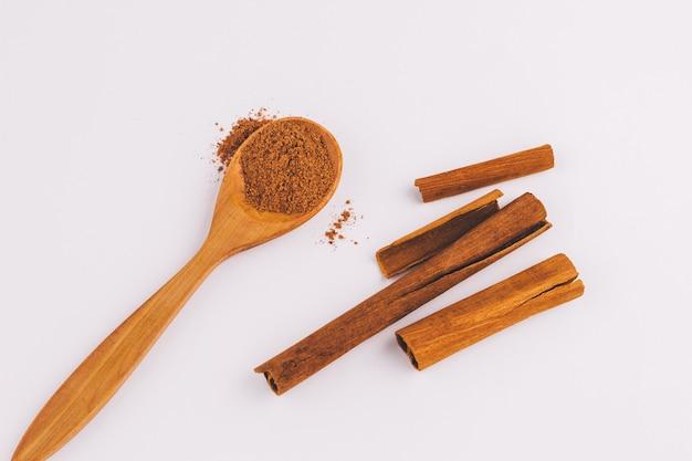 Vista dall'alto di un cucchiaio di legno di sandalo con cannella su sfondo chiaro