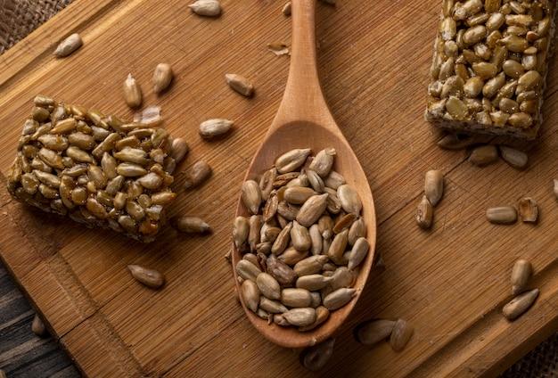Vista dall'alto di un cucchiaio di legno pieno di semi di girasole con kozinaki dolce su legno