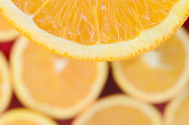 Vista dall'alto di un frammento della fetta di frutta arancione sullo sfondo di molte fette di arancia offuscata.