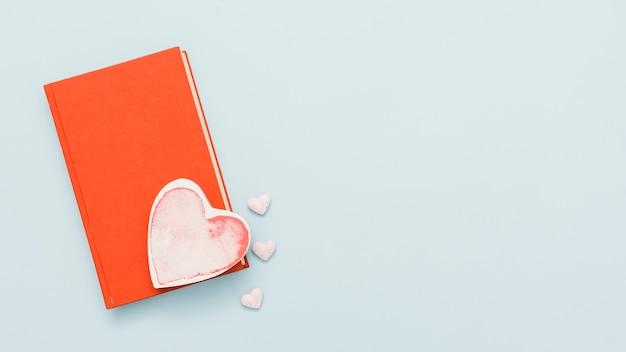 Vista dall'alto di un libro con una carta a forma di cuore