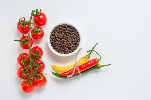 Vista dall'alto di un mazzo di pomodori con una ciotola di pepe nero, peperoncino su sfondo bianco. spazio orizzontale per il testo