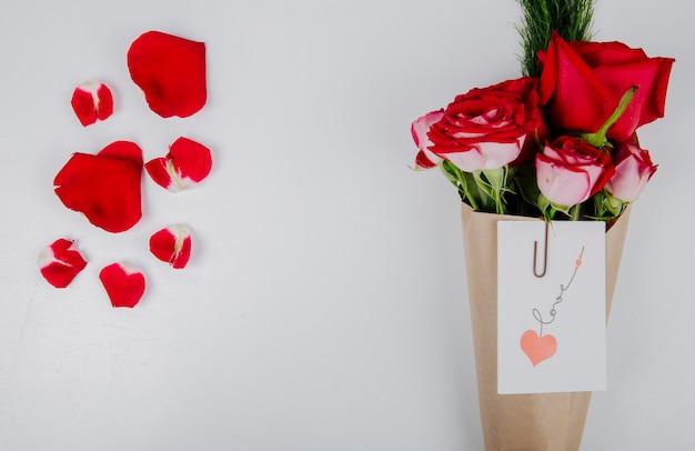 Vista dall'alto di un mazzo di rose di colore rosso con asparagi in carta artigianale con allegata cartolina con una graffetta e petali di fiori rossi su sfondo bianco con spazio di copia