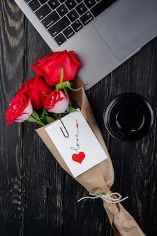 Vista dall'alto di un mazzo di rose rosse in carta artigianale con allegata cartolina sdraiato vicino a un computer portatile con una tazza di caffè di carta su fondo di legno scuro