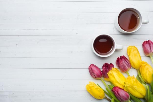 Vista dall'alto di un mazzo di tulipani e una tazza di caffè. copia spazio. vista piana, vista dall'alto
