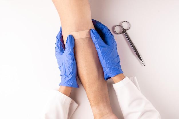 Vista dall'alto di un medico che guarisce una ferita con un nastro o un cerotto.