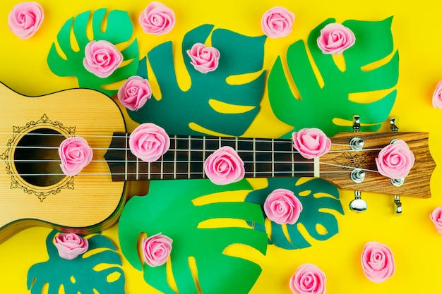 Vista dall'alto di un modello di fiori rosa e chitarra su sfondo giallo vibrante