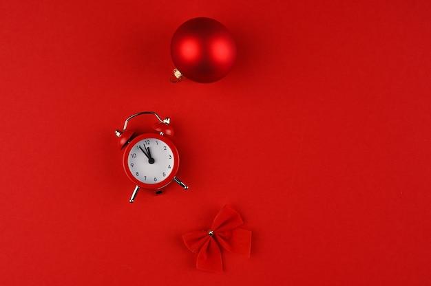 Vista dall'alto di un orologio e decorazioni natalizie rosse su sfondo di carta rossa con spazio di copia.