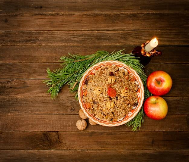Vista dall'alto di un piatto del tradizionale piatto natalizio slavi - kutia. ramo attillato del fondo di legno, mele. spazio per il testo