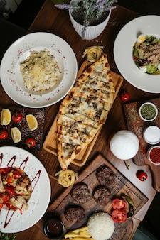 Vista dall'alto di un piatto tradizionale turco carne pide con formaggio su un supporto e altri piatti e spezie sul tavolo