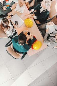 Vista dall'alto di un piccolo gruppo di architetti in abiti da cerimonia seduti a tavola e portare a termine il progetto. i veri leader non creano seguaci, creano più leader.