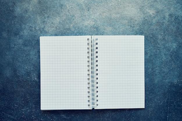 Vista dall'alto di un quaderno aperto con pagine quadrate vuote. quaderno di scuola su sfondo blu, blocco note a spirale. torna al concetto di scuola