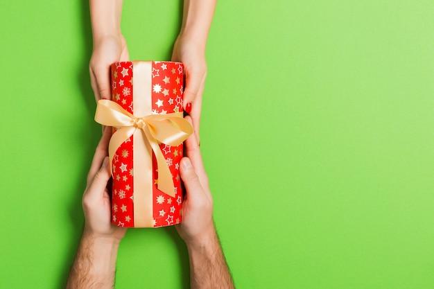 Vista dall'alto di un regalo in mani maschili e femminile su sfondo colorato
