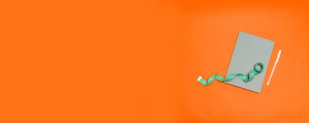 Vista dall'alto di un taccuino grigio con penna e nastro di misurazione su uno sfondo arancione con spazio di copia.