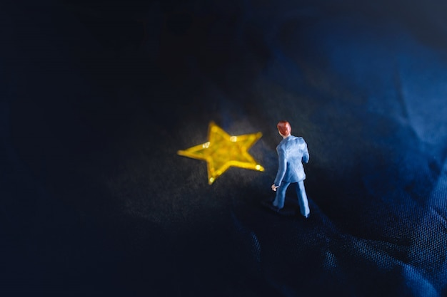 Vista dall'alto di un uomo d'affari in miniatura in piedi su una stella d'oro gialla